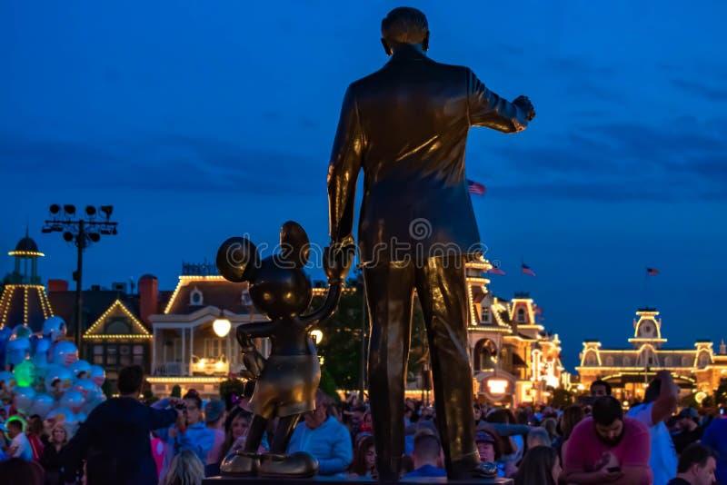Vista trasera de las estatuas de los socios Walt Disney y de Mickey Mouse en fondo azul de la noche en el reino mágico fotografía de archivo libre de regalías