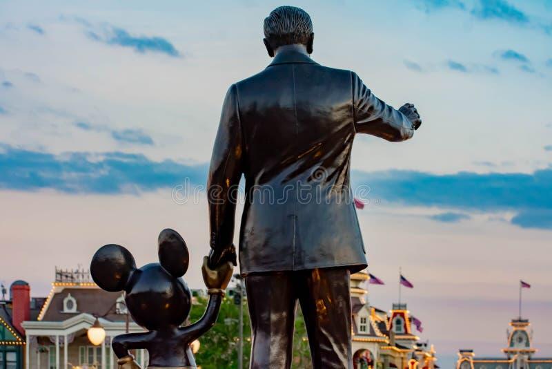 Vista trasera de las estatuas de los socios Walt Disney y de Mickey Mouse en fondo de la puesta del sol en el reino mágico foto de archivo libre de regalías