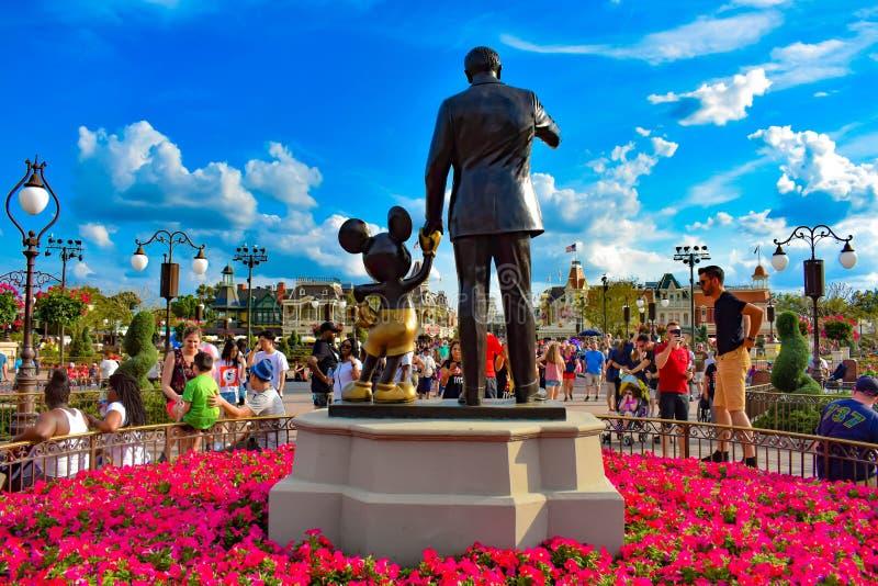 Vista trasera de las estatuas de los socios Walt Disney y de Mickey Mouse y de las flores coloridas en el reino mágico fotografía de archivo