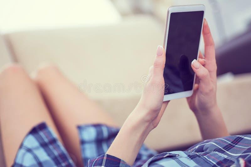 Vista trasera de las manos de una mujer usando el teléfono elegante con cierre de la pantalla en blanco para arriba Teléfono blan fotografía de archivo