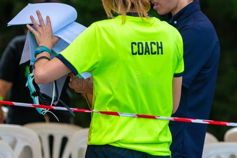 Vista trasera de los coachers que nadan femeninos que miran sobre su interruptor del equipo fotos de archivo libres de regalías