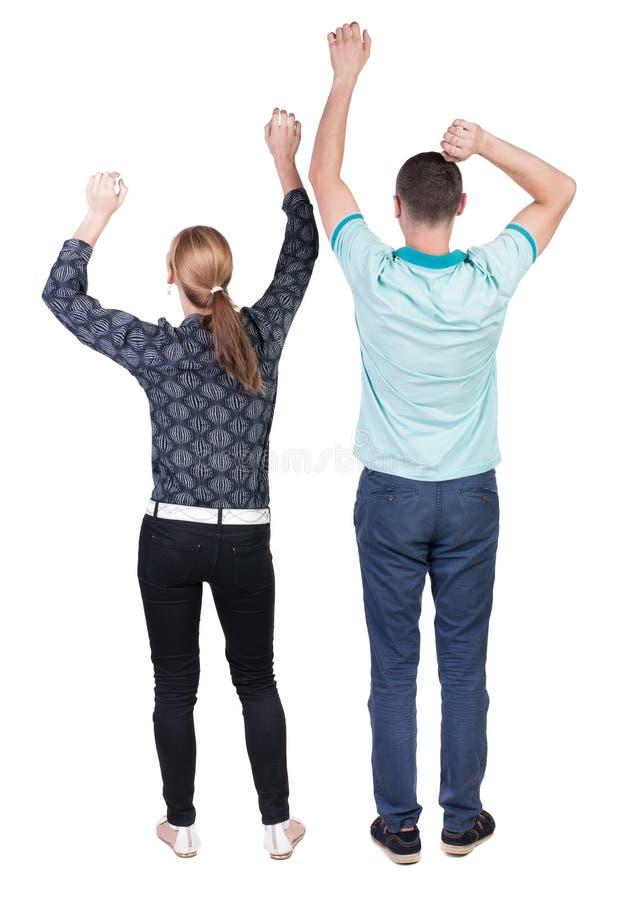 Vista trasera de los pares alegres que celebran las manos de la victoria para arriba fotos de archivo libres de regalías