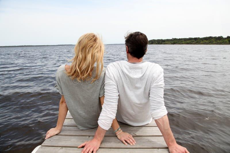 Vista trasera de los pares jovenes que se sientan por el lago fotografía de archivo