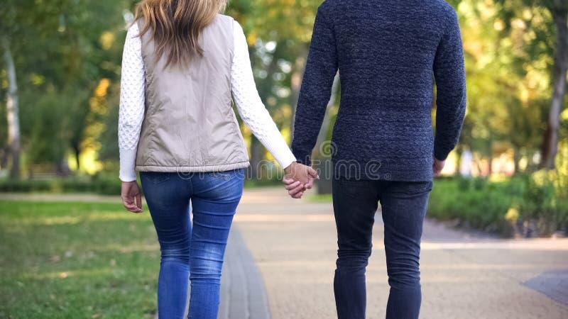 Vista trasera de los pares que llevan a cabo las manos y que caminan con confianza en futuro brillante foto de archivo libre de regalías