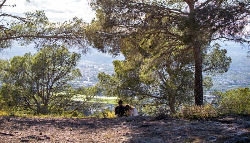 Vista trasera de pares románticos en el amor que se sienta en campo de hierba y que mira la puesta del sol sobre el paisaje urba foto de archivo
