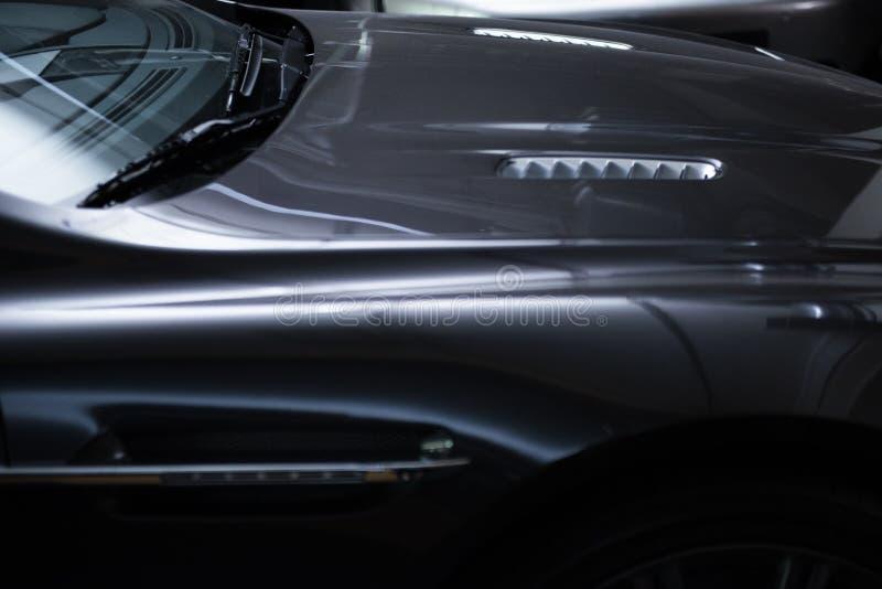 Vista trasera de un coche metálico gris de lujo moderno, detalle auto, concepto del mantenimiento del coche en el garaje foto de archivo