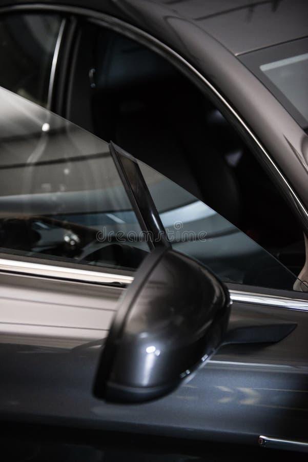 Vista trasera de un coche metálico negro gris de lujo moderno, detalle auto, concepto del mantenimiento del coche en el garaje imágenes de archivo libres de regalías