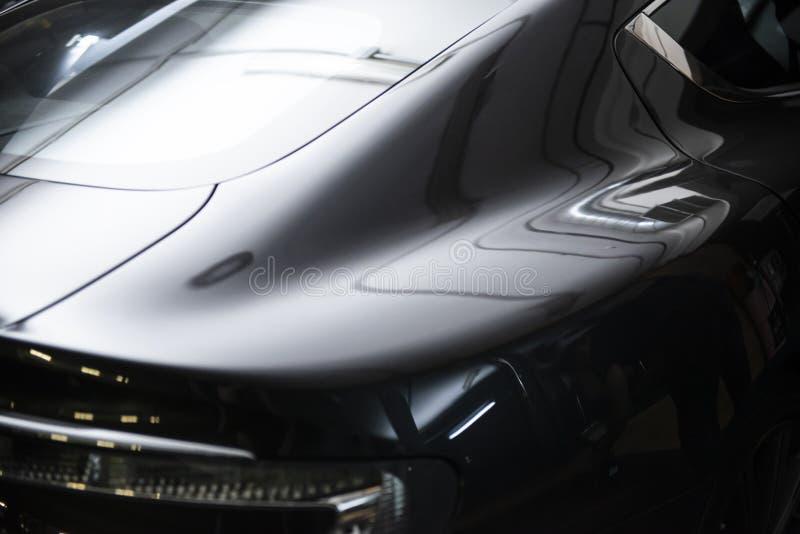 Vista trasera de un coche metálico negro gris de lujo moderno, detalle auto, concepto del mantenimiento del coche en el garaje foto de archivo libre de regalías