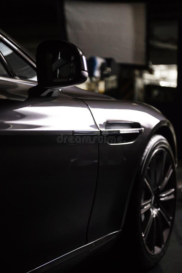Vista trasera de un coche metálico negro gris de lujo moderno, detalle auto, concepto del mantenimiento del coche en el garaje fotos de archivo