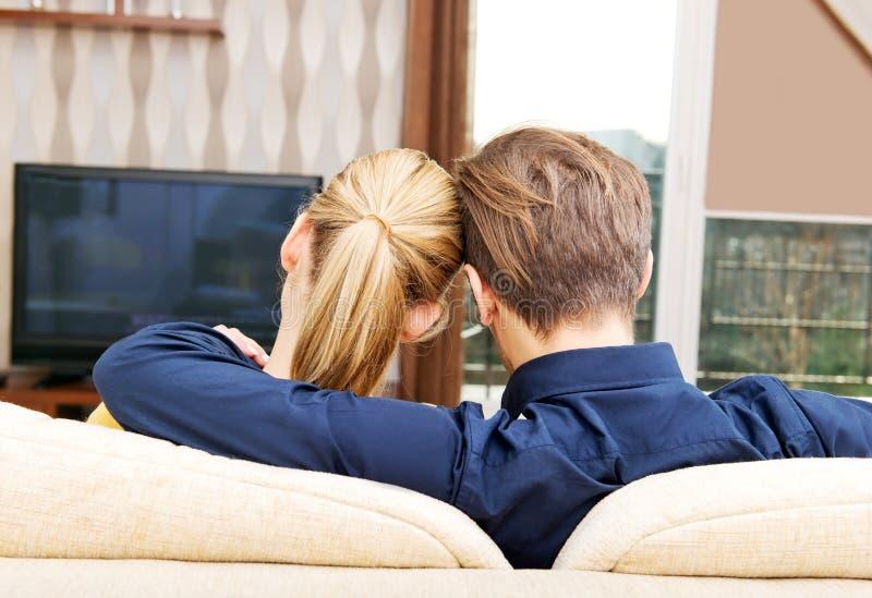 Vista trasera de un par que ve la TV en casa fotos de archivo