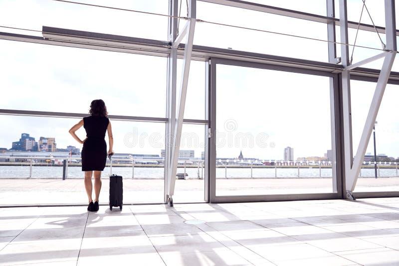 Vista Trasera De Una Mujer De Negocios Con Equipaje Parado Por Una Ventana En El Salón De Salida Del Aeropuerto foto de archivo