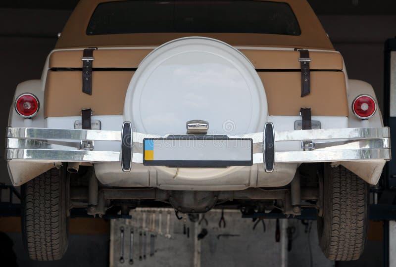 Vista trasera del coche de la vendimia que cuelga en el garage foto de archivo