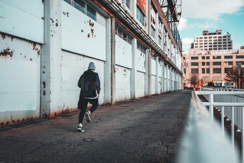Vista trasera del entrenamiento del corredor en puerto de la ciudad fotografía de archivo