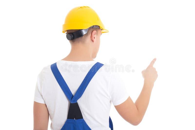 Vista trasera del hombre en uniforme del constructor y del casco que señalan en alguno fotografía de archivo