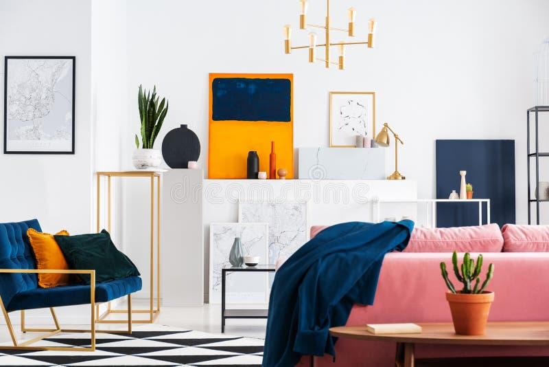 Vista trasera del sofá rosado del polvo en la sala de estar elegante del apartamento del colector del arte por completo de pintur imágenes de archivo libres de regalías
