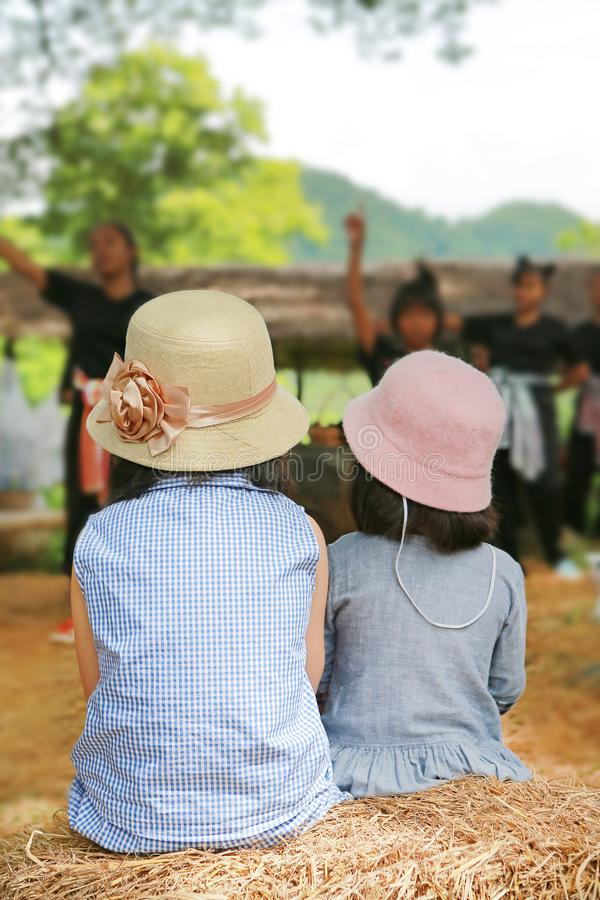 Vista trasera del sombrero que lleva de la muchacha de dos niños que mira la demostración de la cultura en el parque de naturalez foto de archivo libre de regalías