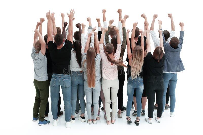 Vista trasera un ambicioso grupo de jóvenes con las manos arriba fotografía de archivo libre de regalías