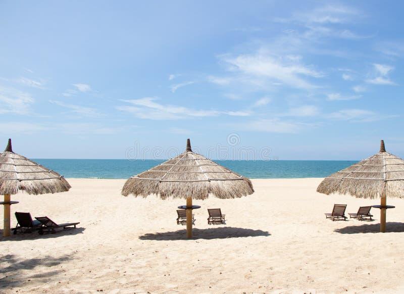 Vista tropicale di una spiaggia con gli ombrelli e le sedie di spiaggia immagine stock libera da diritti