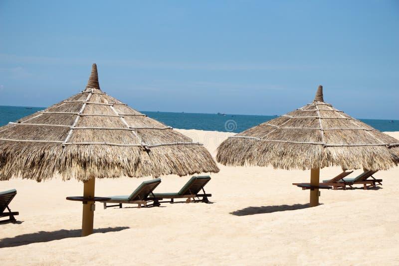Vista tropicale di una spiaggia con gli ombrelli e le sedie di spiaggia fotografia stock