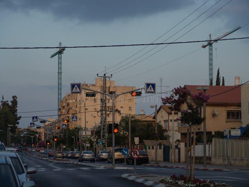 Vista urbana de uma estrada frente e verso vazia com os sinais de passeio iluminados acima na laranja, em carros estacionados e e imagem de stock royalty free