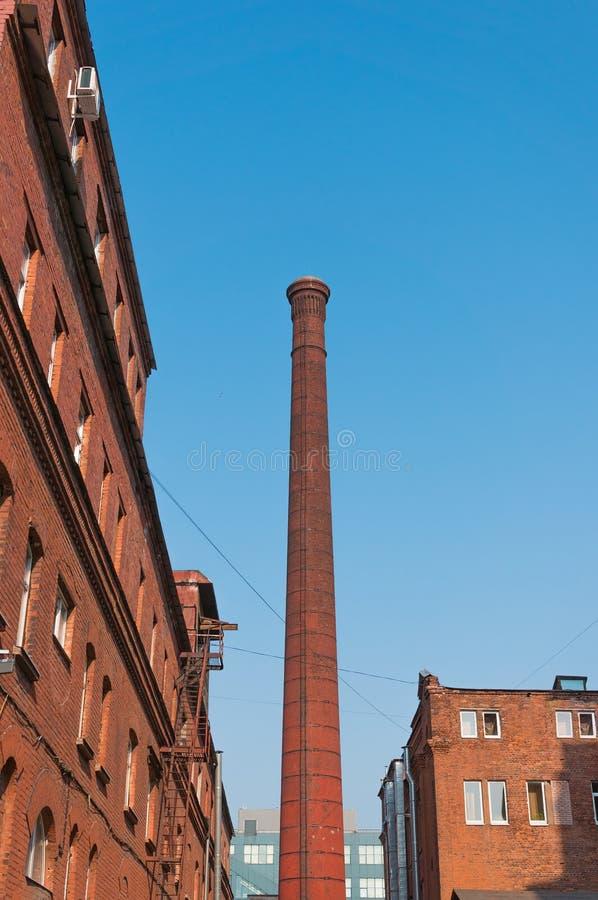 Vista urbana - tubo della fabbrica e vecchie costruzioni di mattone contro il cielo blu immagini stock