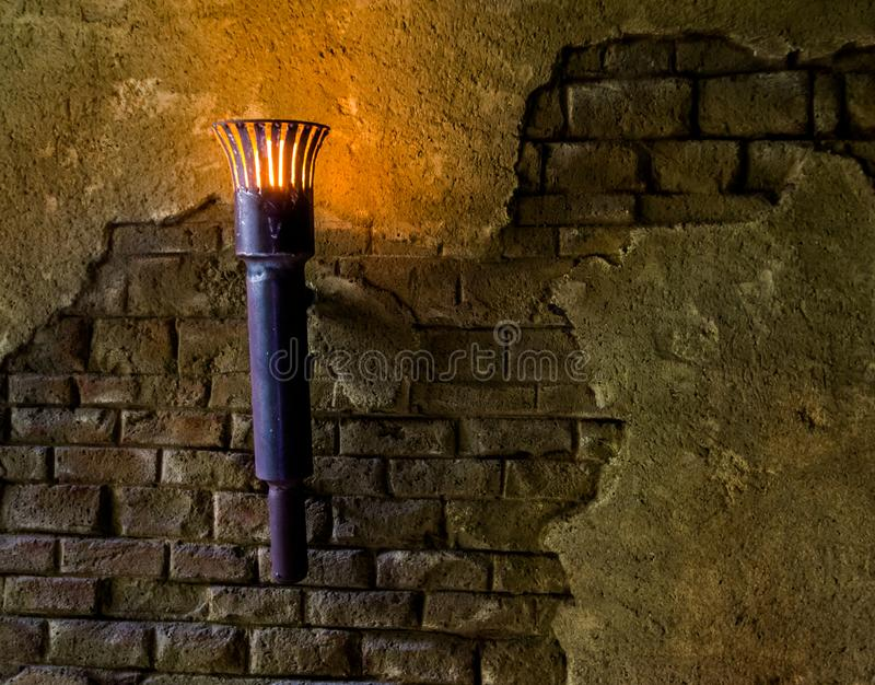 Vista velha e tocha iluminada que penduram em uma parede de pedra, interiores medievais do metal fotos de stock royalty free