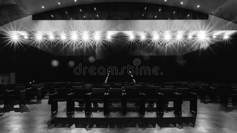 Vista verso i sedili vuoti del pubblico dalla fase con i riflettori intenzionali - monocromio fotografia stock libera da diritti