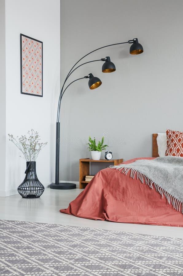 Vista vertical da cobertura cinzenta na cama com os coxins no interior do quarto com lâmpada e plantas fotos de stock royalty free