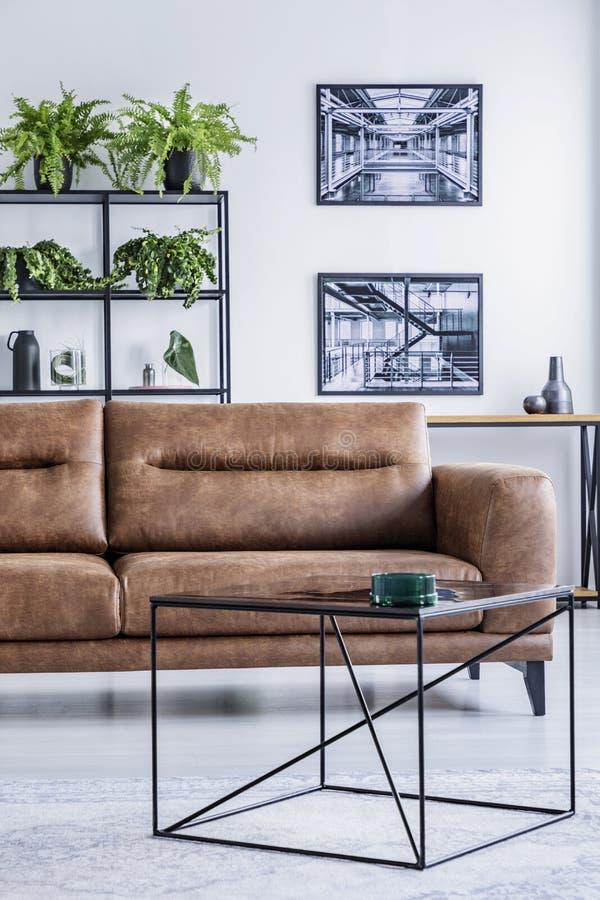 Vista vertical da sala de visitas espaçoso com o canapé de couro confortável, a mesa de centro e os cartazes industriais fotografia de stock