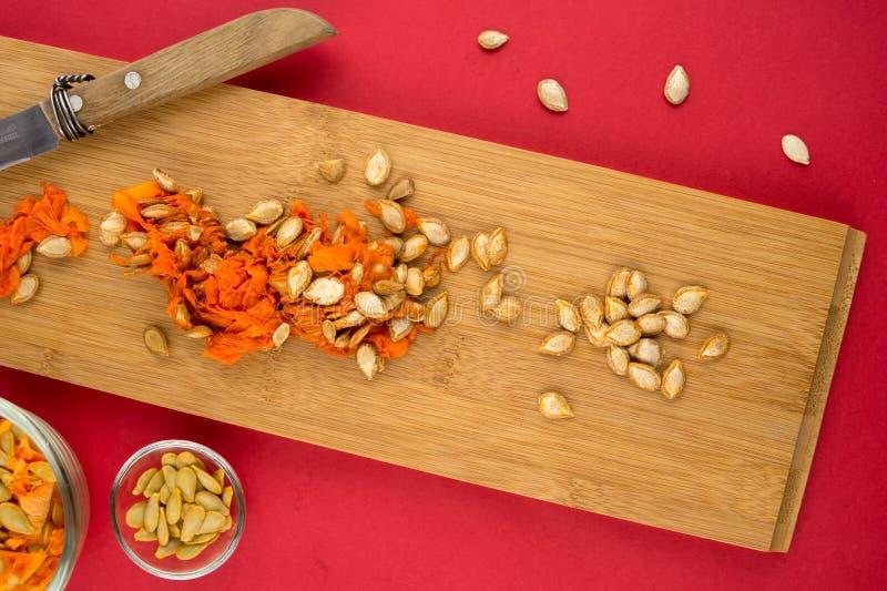 Vista vertical de la carne y de las semillas de la calabaza en tabla de cortar imagen de archivo libre de regalías