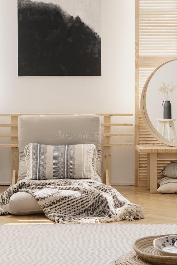 Vista vertical de la pintura abstracta blanco y negro sobre la manta caliente blanca y la almohada modelada en futon beige en nat imágenes de archivo libres de regalías