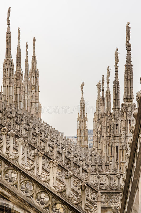 Vista vertical de las esculturas de piedra en los tejados del Duomo Milano imágenes de archivo libres de regalías