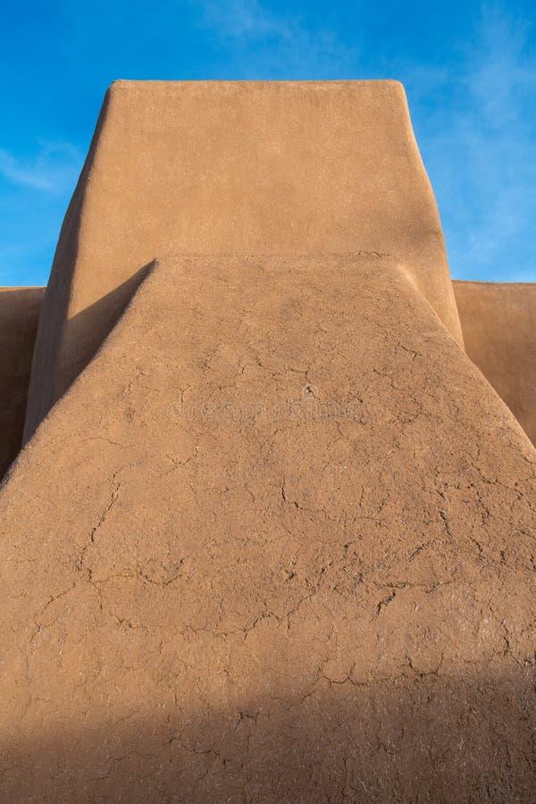 Vista vertical de las paredes del adobe y arquitectura de una iglesia española vieja de la misión en New México imágenes de archivo libres de regalías