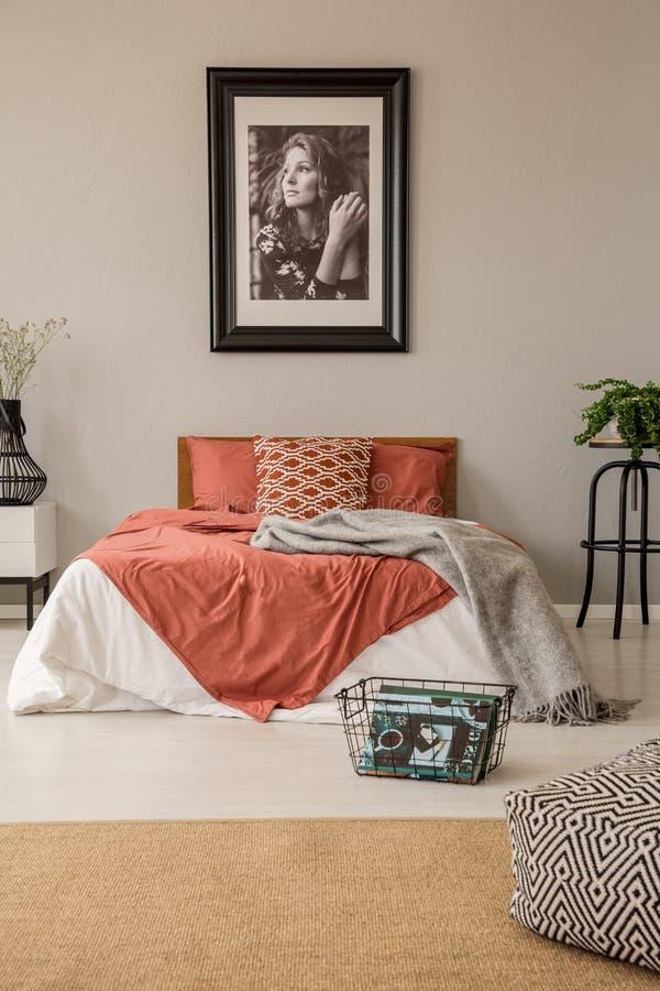 Vista vertical del dormitorio con la cama gigante con las almohadas, edredón y manta y cartel en marco en la pared imagenes de archivo