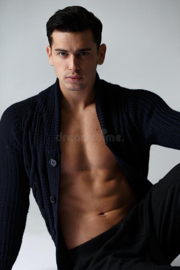 Vista vertical Homem considerável com o torso despido na roupa preta, olhando a câmera, no fundo branco imagens de stock royalty free