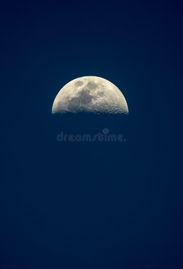 Vista vertical impar de uma meia lua brilhante clara em um céu noturno azul foto de stock royalty free