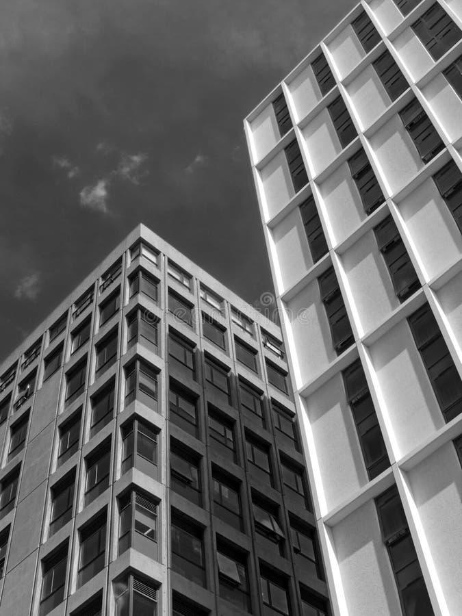 Vista vertical monocromática de um céu nebuloso branco alto branco de construções concretas imagens de stock