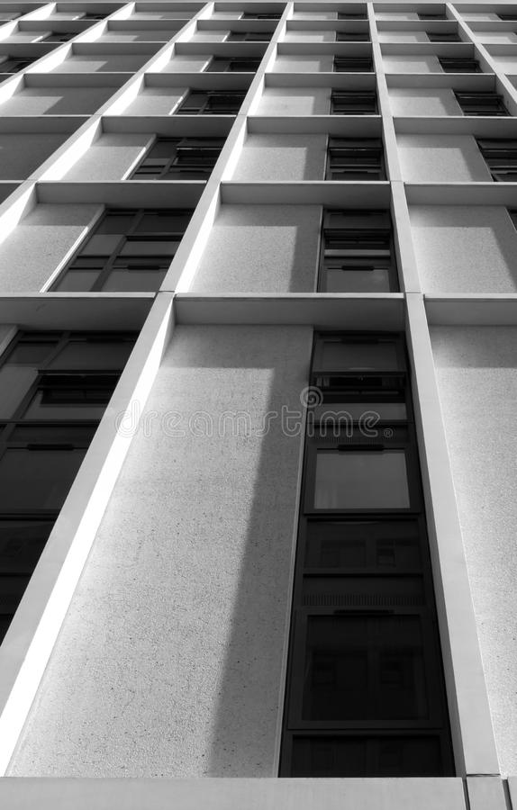 Vista vertical monocromática de uma construção alta moderna angular concreta alta com detalhes brancos geométricos foto de stock