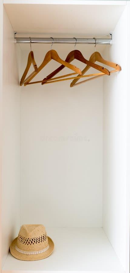 Vista verticale del dettaglio degli appendiabiti vuoti in un guardaroba bianco con un cappello della fedora della paglia fotografia stock