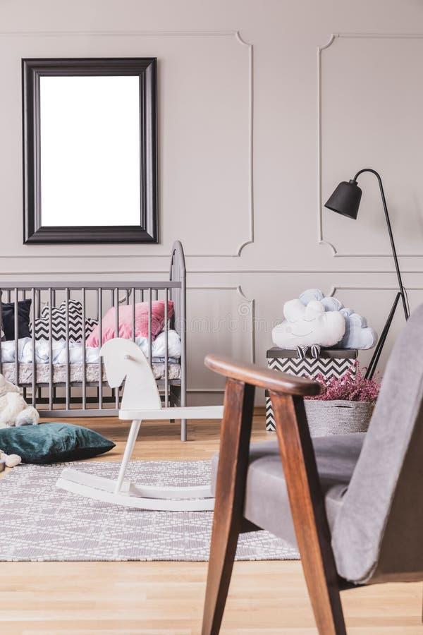 Vista verticale della poltrona grigia d'annata nella stanza d'avanguardia del bambino di metà del secolo interna con il modello n immagini stock libere da diritti