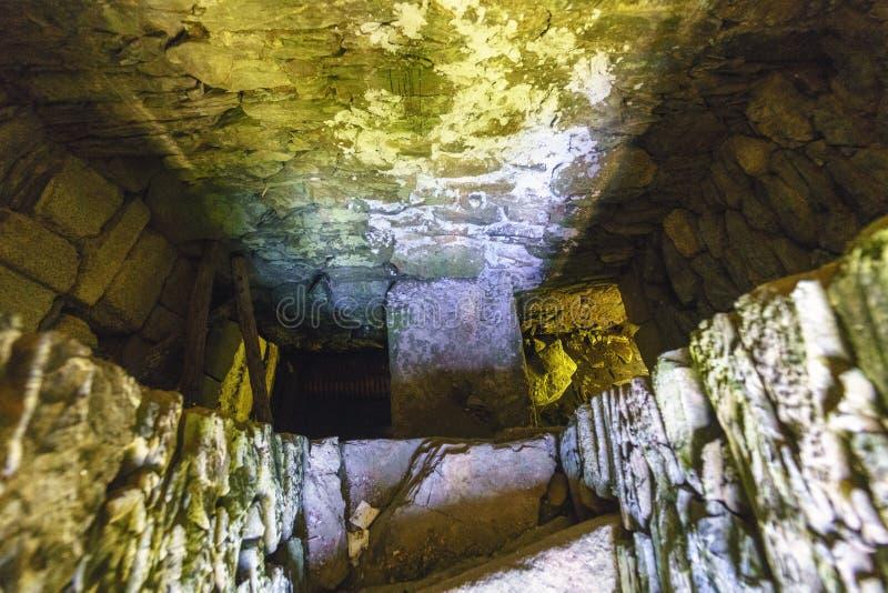Vista verticale di un asciutto bene con le pareti di pietra ed acqua antica e fotografie stock libere da diritti
