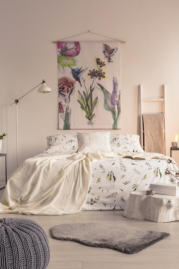 Vista verticale di un interno pastello della camera da letto con un grande letto nel mezzo ed in un'arte dipinta del tessuto sull fotografia stock