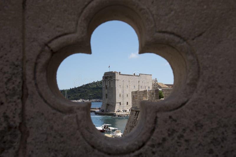 Vistas, através de um buraco em forma de cruz localizado numa ponte, das paredes de pedra e do porto de Dubrovnik, Croácia imagem de stock