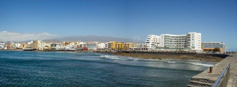Vistas cênicos da manhã para a vila do EL Medano do cais com as construções pitorescas e da praia pequena na parte dianteira, e fotografia de stock