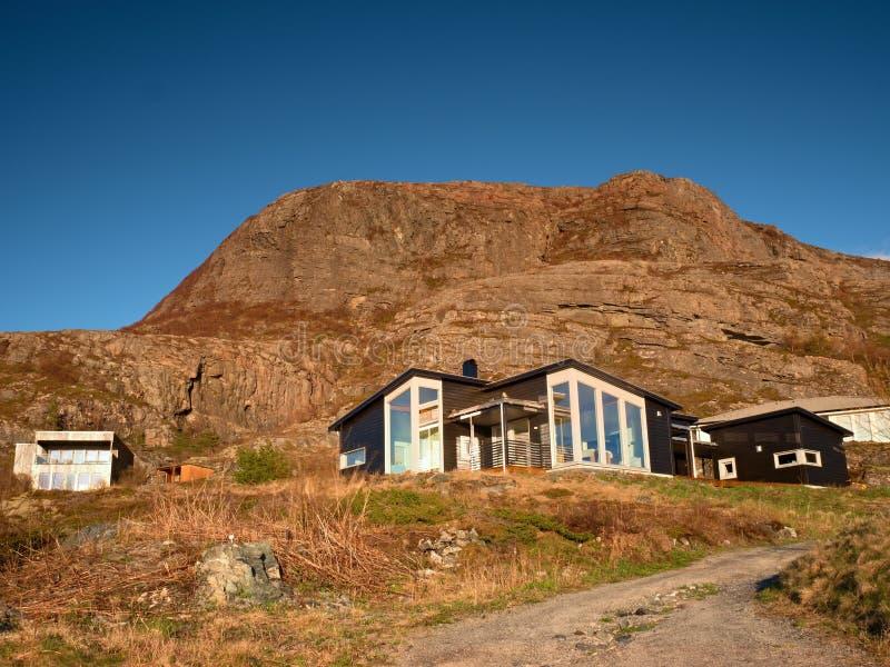 Vistas de la orilla de mar, pasando por alto las cabañas típicas de la costa, en Noruega imagen de archivo libre de regalías