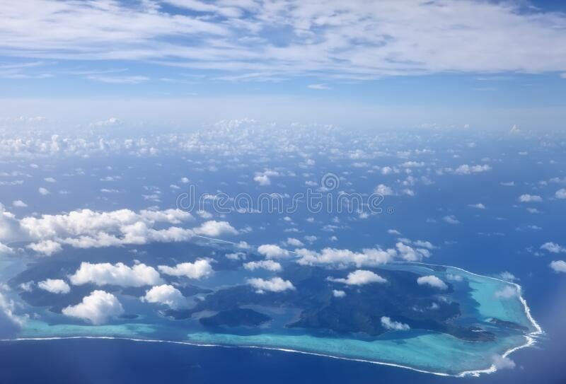 Vistas desde el avión a las islas de coral en el mar bajo las nubes, Polinesia, Tahití fotos de archivo