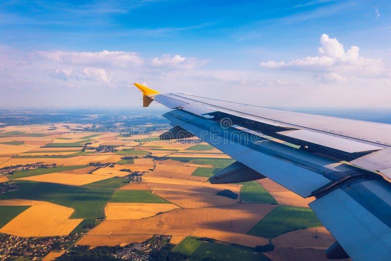 Vistas do avião sobre a Terra em ponto de referência Vista de uma janela de um avião sobre uma asa voando acima de terras agrícol foto de stock