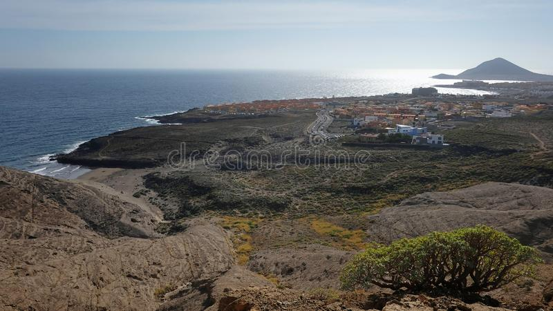 Vistas elevados dos owards da montanha de Pelada a cidade costeira do windsurfe do EL Medano e com Montana Roja na extremidade foto de stock