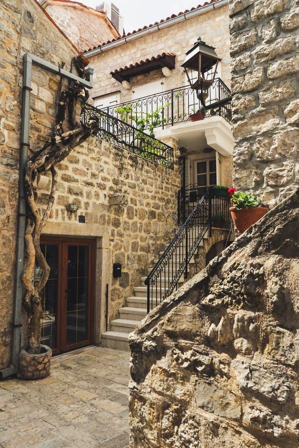 Viste e vie di vecchia città di Budua, Montenegro Case e pareti di pietra antiche nel centro della città con le scale e fotografie stock