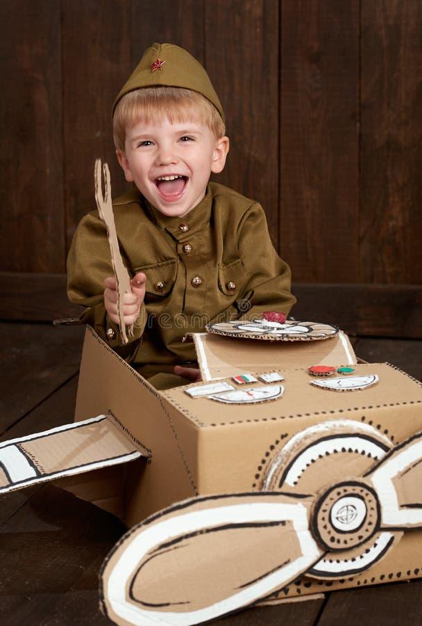 Visten al muchacho de los niños como el soldado en uniformes militares retros repara un aeroplano hecho de la caja de cartón, fon fotografía de archivo libre de regalías